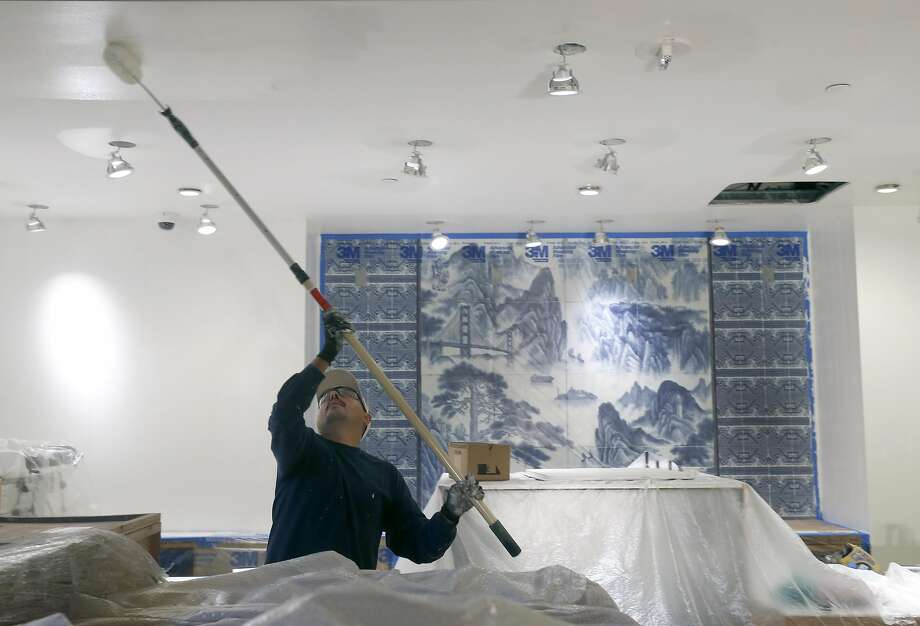In the soon-to-open, 30,000-square-foot China Live complex, Luis Cardenas applies a coat of paint to the ceiling of Oolong Cafe, whose specialty will be teas from China and Taiwan. Photo: Paul Chinn, The Chronicle