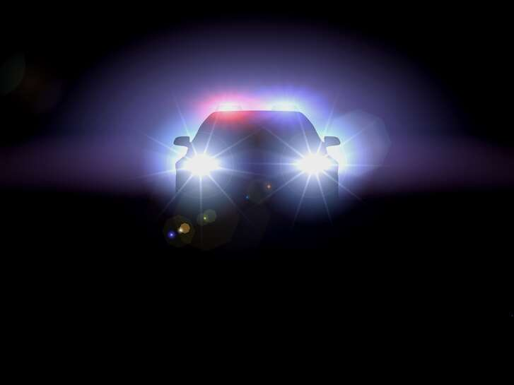 HEADLIGHTS OF POLICE CAR AT NIGHT