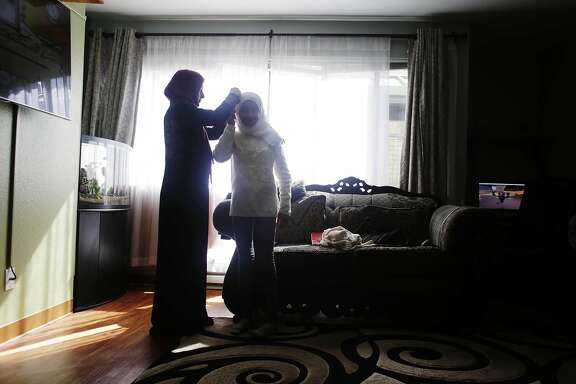 Bushra Alduais (l to r) adjusts her daughter, Malak Alameri's, 11, scarf while visiting family members at her her sister-in-law Nadia Rashed's (not shown) home on Wednesday, February 22, 2017 in San Francisco, Calif.