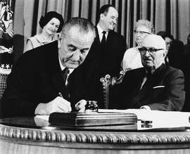 FILE - In this July 30, 1965 file photo, President Lyndon Johnson signs the Medicare Bill into law while former President Harry S. Truman, right, observes during a ceremony at the Truman Library in Independence, Mo. At rear are Lady Bird Johnson, Vice President Hubert Humphrey, and former first lady Bess Truman. When Johnson signed Medicare and Medicaid into law Americans 65 and older were the age group least likely to have health insurance.  (AP Photo)
