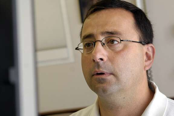 FILE - In this July 15, 2008, file photo, Dr. Larry Nassar works on the computer after seeing a patient in Michigan. Nassar, accused of sexual abuse by two gymnasts, has been fired by Michigan State University, eniversity spokesman Jason Cody said Tuesday, Sept. 20, 2016. (Becky Shink/Lansing State Journal via AP, File)