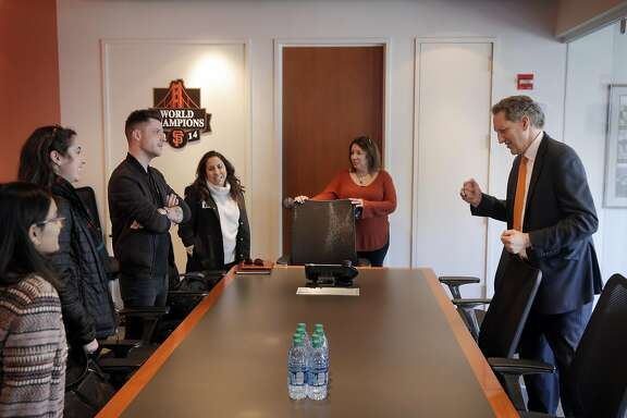 Larry Baer, CEO of the San Francisco Giants, right, stops to have a word with several guests in the Giants offices at AT&T Park in San Francisco, Calif., on Wednesday, February 22, 2017.
