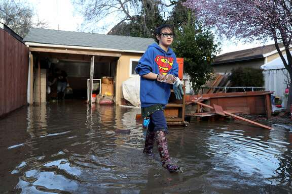 Jillian McLane, 11, helps out in the clean up effort at her friend's house after flood waters from Coyote Creek inundated 20th Street in San Jose, Calif., on Wednesday, February 22, 2017.