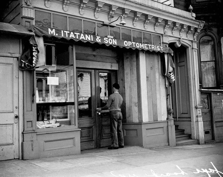 On April 6, 1942, a San Francisco store-owner of Japanese descent boards up and closes his optometry shop before leaving for a U.S. internment camp during World War II. Photo: Chronicle File Photo, The Chronicle