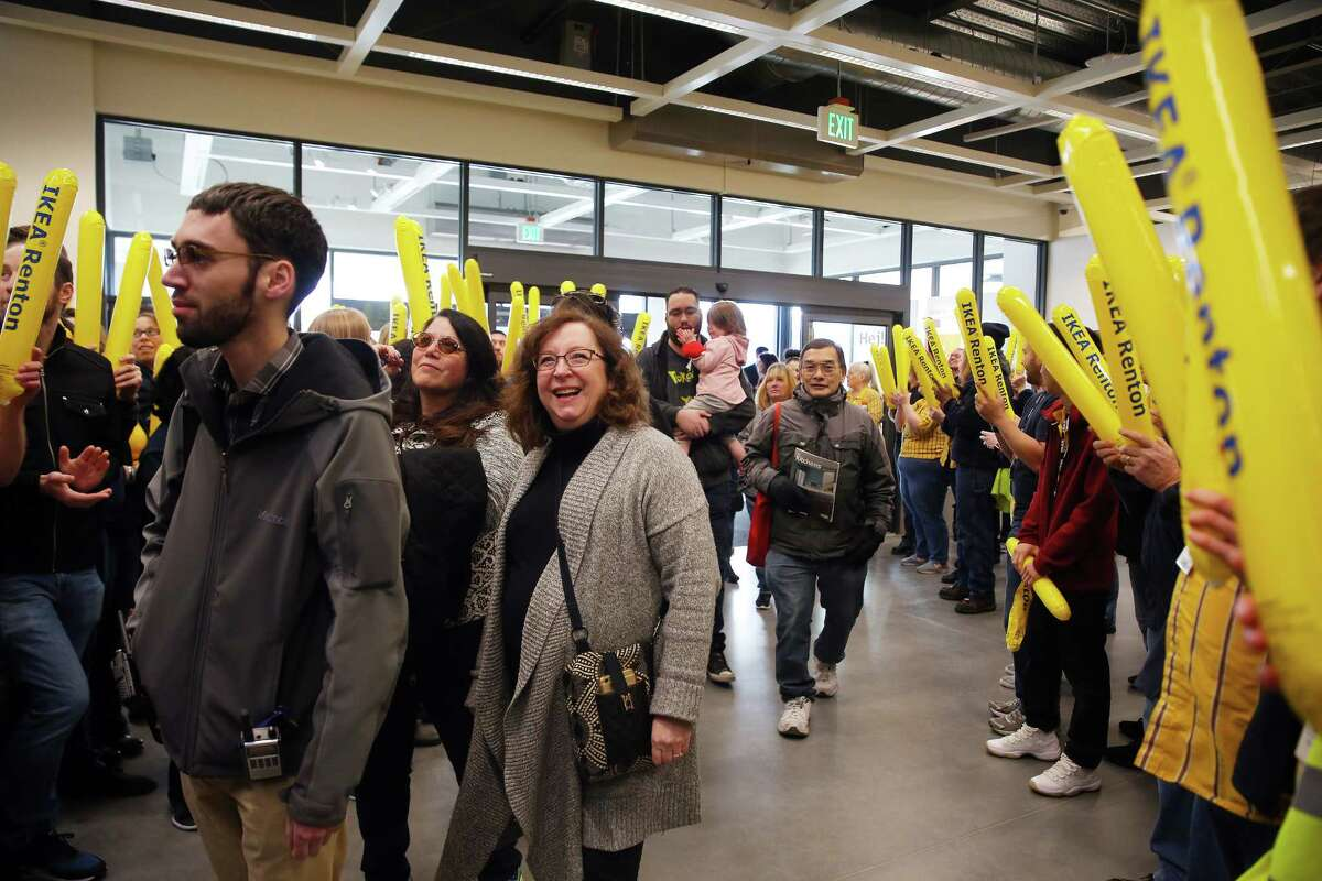 Employees line up and cheer as the first members of the public enter the new Ikea store in Renton.
