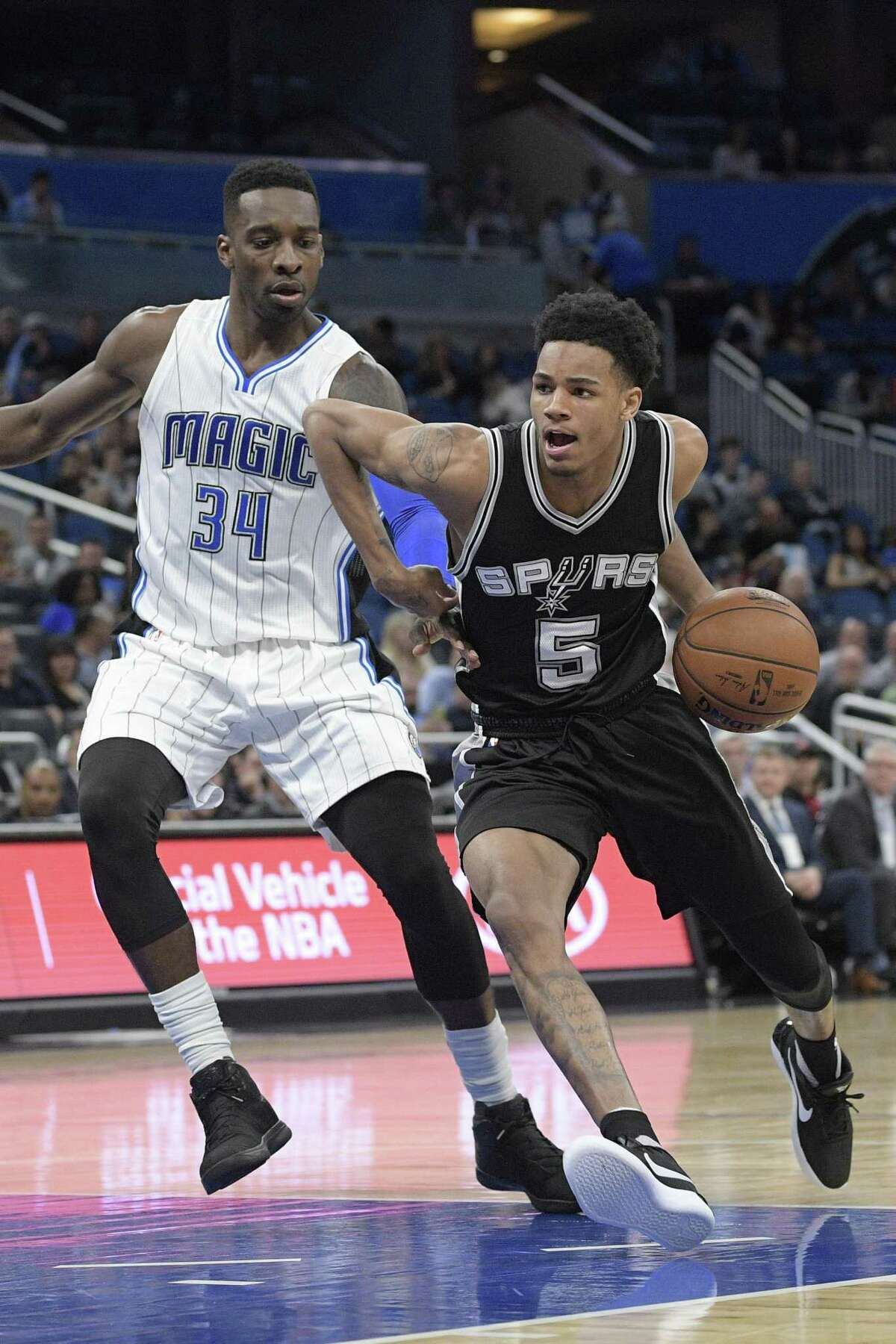 San Antonio Spurs guard Dejounte Murray (5) drives to the basket in front of Orlando Magic forward Jeff Green (34) during the second half of an NBA basketball game in Orlando, Fla., Wednesday, Feb. 15, 2017. The Spurs won 107-79. (AP Photo/Phelan M. Ebenhack)