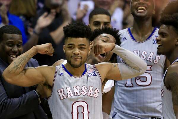 Kansas guard Frank Mason III (0) celebrates with teammates on the bench during the second half of the team's NCAA college basketball game against TCU in Lawrence, Kan., Wednesday, Feb. 22, 2017. Mason scored 20 points as Kansas defeated TCU 87-68. The Jayhawks clinched at least a tie for their 13th straight Big 12 title. (AP Photo/Orlin Wagner)