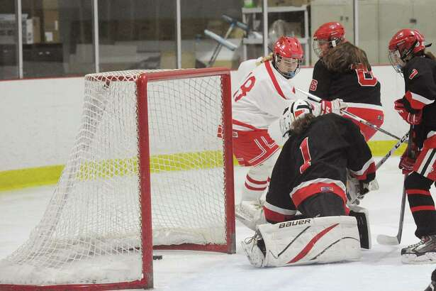 Greenwich's Jen Kelly, center, beats New Canaan goalie Kara Fahey to score the first goal of the game Wednesday at the Darien Ice Rink.