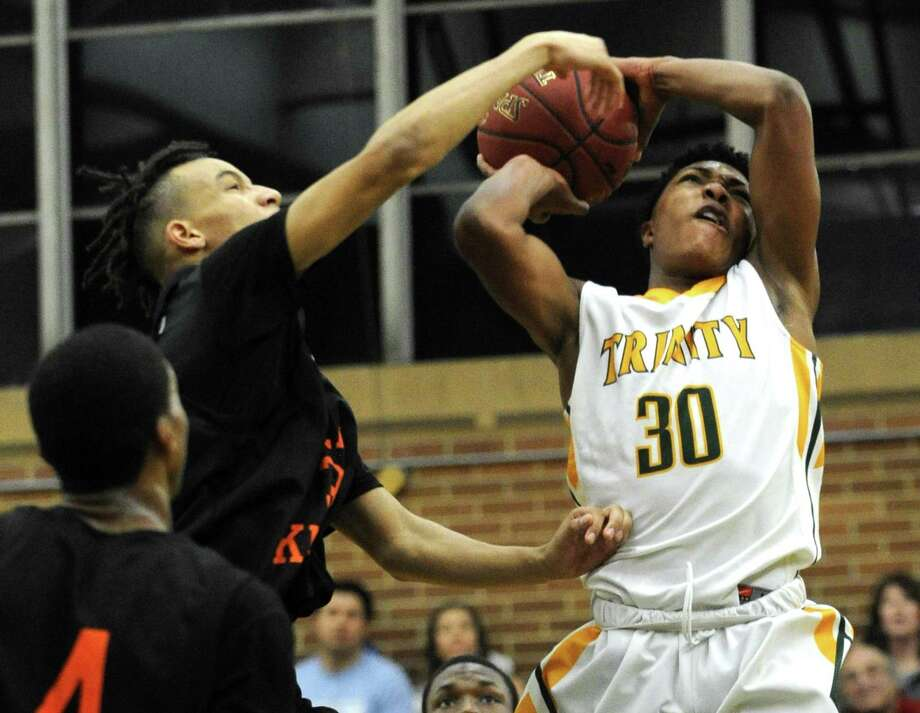 Stamford Malcolm D'Angelo fouls Trinity Rasheed Constant on his shot in a boys basketball game at Trinity Catholic High School's Walsh Court in Stamford on Feb. 22, 2017. Trinity defeated Stamford 75-70. Photo: Matthew Brown / Hearst Connecticut Media / Stamford Advocate