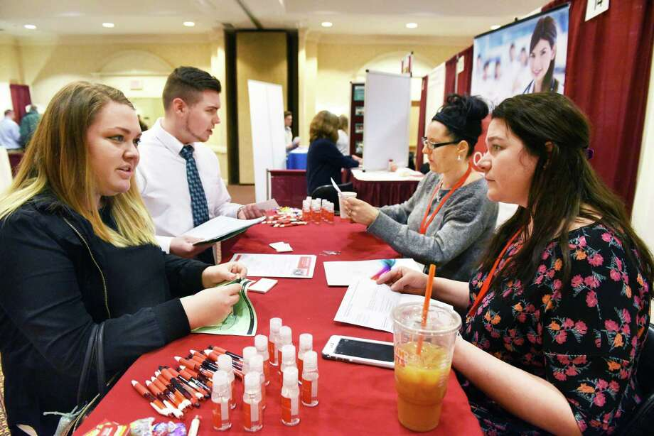 Erika Tessitore, left, and Brandon Barber of Watervliet speak with St. Peter's recruiters Audrey Scialdone and Samantha Stewart, right, during the annual Times Union health careers job fair Wednesday Feb. 22, 2017, in Colonie, NY.  (John Carl D'Annibale / Times Union) Photo: John Carl D'Annibale / 40039757A