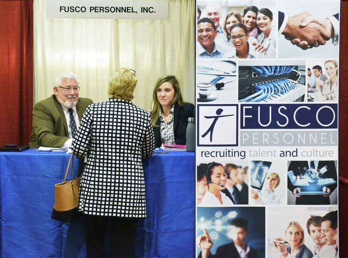 Dr. Joseph Monahan, left, and Lindsay Pierce of Fusco Personnel speak with a job seeker during the annual Times Union health careers job fair Wednesday Feb. 22, 2017, in Colonie, NY. (John Carl D'Annibale / Times Union)