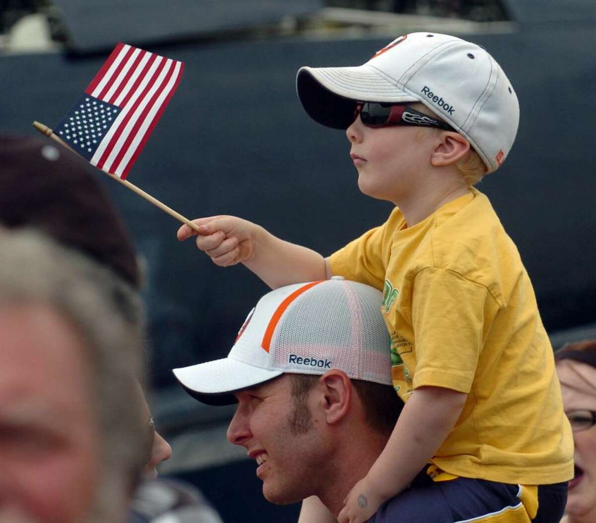 Aiden Courtney, of Bridgeport, waves the US flag while sitting atop his dad Chris' shoulders, during the Wings and Wheels 2010 car and air show at Sikorsky Memorial Airport in Stratford, Conn. on Saturday May 29, 2010.