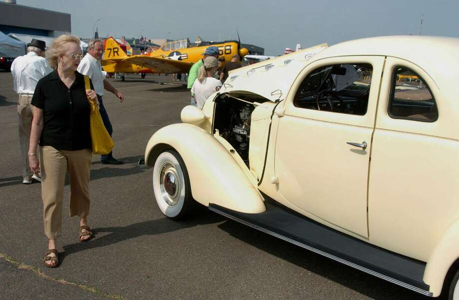 Pam Beighley, of Jacksonville, FL, checks out a 1937 Graham Supercharged Coupe, during the Wings and Wheels 2010 car and air show at Sikorsky Memorial Airport in Stratford, Conn. on Saturday May 29, 2010.  The Graham is owned by Tom and Marie Tkacz, of Seymour. Photo: Christian Abraham / Connecticut Post