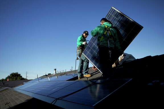 FILE -- Workers from Solar City install photovoltaic panels on the roof of a house in San Leandro, Calif., Dec. 9, 2013. The company, owned by Tesla, relies on monthly payments from solar panel customers. But foreclosures can halt those payments, and SolarCity relies on only one credit check to vet customers. (Thor Swift/The New York Times)