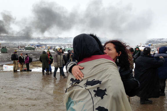 A couple embrace as opponents of the Dakota Access pipeline leave their main protest camp Wednesday near Cannon Ball, N.D., as authorities were preparing to shut down the camp in advance of spring flooding season. The Army Corps of Engineers ordered the camp closed Wednesday afternoon.