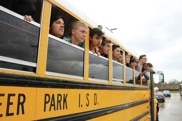 Forced to wait out a lightning delay in the team bus, the Deer Park boys track and field team poke their heads out of the bus to check out the improving weather conditions before the Brown Relays resumed last Friday.