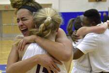 Bethel team captains Amanda Towey and Margaret Dolan (15) hug after Bethel defeated New Fairfield 44-37 in the SWC girls basketball championship Wednesday at Newtown High School.