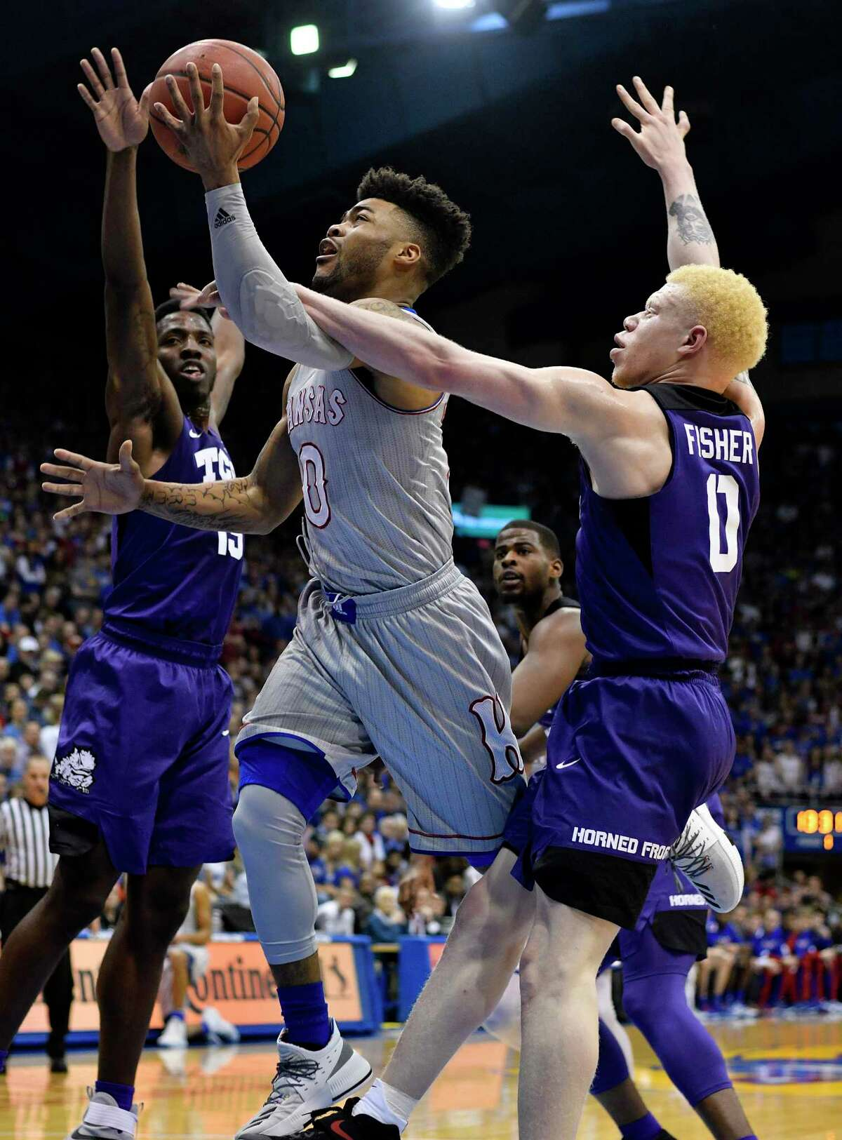 LAWRENCE, KS - FEBRUARY 22: Frank Mason III #0 of the Kansas Jayhawks lays the ball up against JD Miller #15 and Jaylen Fisher #0 of the TCU Horned Frogs in the first half at Allen Fieldhouse on February 22, 2017 in Lawrence, Kansas. (Photo by Ed Zurga/Getty Images) ORG XMIT: 669708613