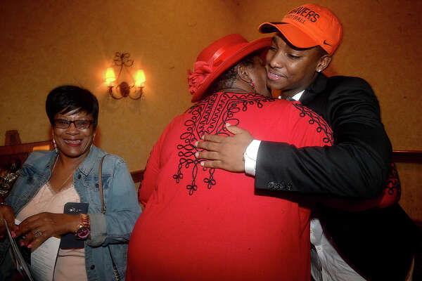 Offensive winner Calvin Tyler of Silsbee gets a warm hug of congratulations from Beatrice Guidry of Orange as Linda Reddix looks on following the award presentation the annual Willie Ray Smith Awards ceremony Wednesday night at the MCM Elegante Hotel. The region's top offensive and defensive players were honored at the event, which is sponsored by the Beaumont Founders Lions Club and in its 25th year. Photo taken Wednesday, February 22, 2017 Kim Brent/The Enterprise