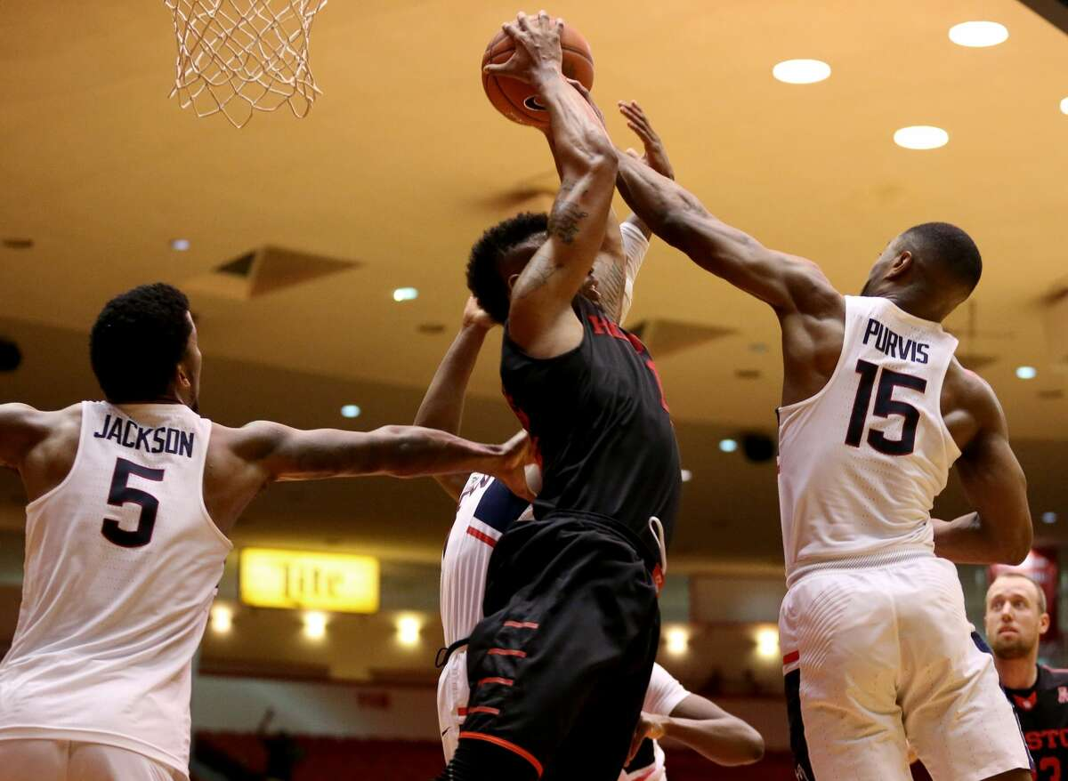 Houston Cougars forward Devin Davis (15) fights with Connecticut Huskies players Vance Jackson (5) and Rodney Purvis (15) for a rebound during the second half of the game Wednesday, Feb. 22, 2017, in Houston. ( Yi-Chin Lee / Houston Chronicle )