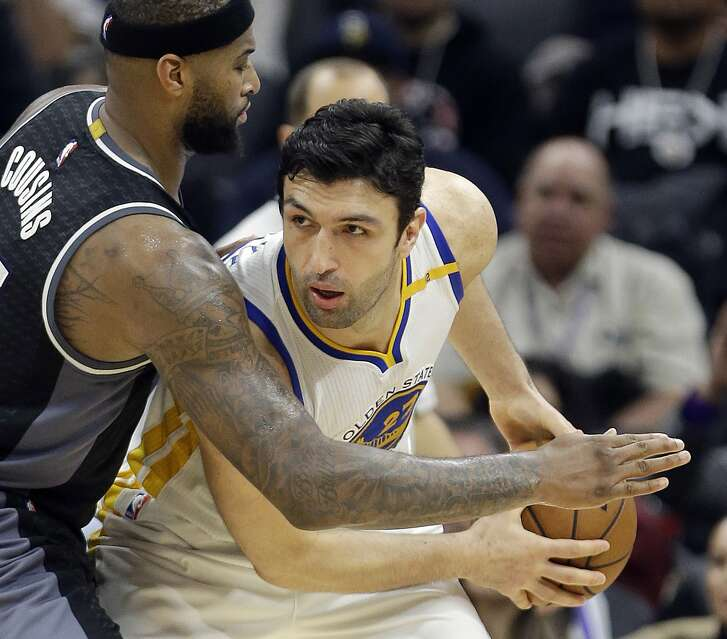 FILE - In this Jan. 8, 2017 file photo, Golden State Warriors center Zaza Pachulia looks past Sacramento Kings forward DeMarcus Cousins during the team's NBA basketball game in Sacramento, Calif. Pachulia is among quite a few Warriors who build team chemistry on flights between games by playing very competitive games of poker. With all that was made before the season about adding Kevin Durant to an already star-studded roster, Golden State's players have jelled just fine. (AP Photo/Rich Pedroncelli, File)