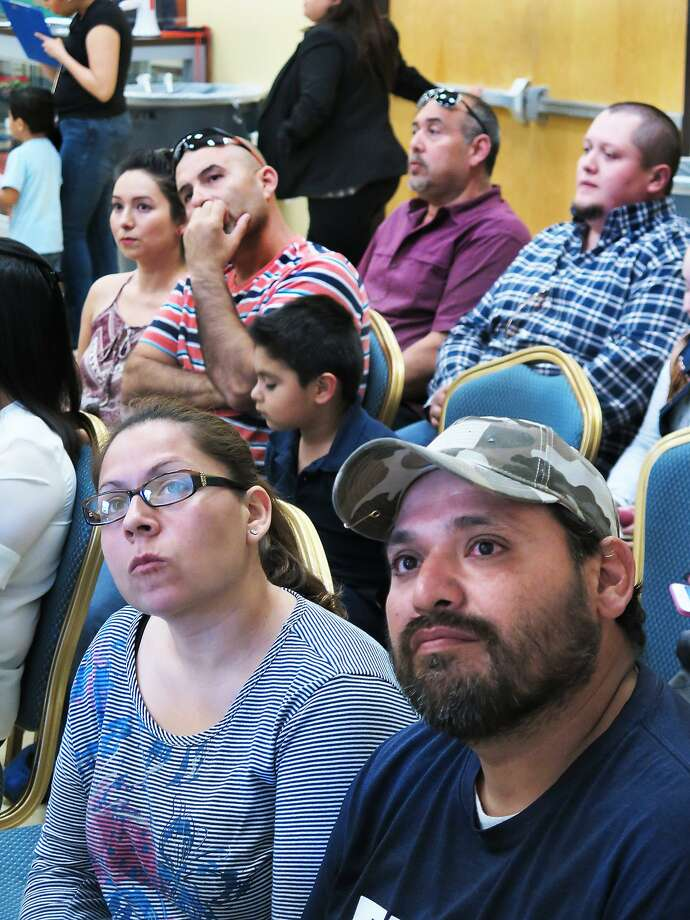 Yuridia and Victor Solis, in foreground, look at a chart indicating the number of slots available for Harmony elementary and middle school students on Wednesday. Photo: Cuate Santos /Laredo Morning Times / Laredo Morning Times