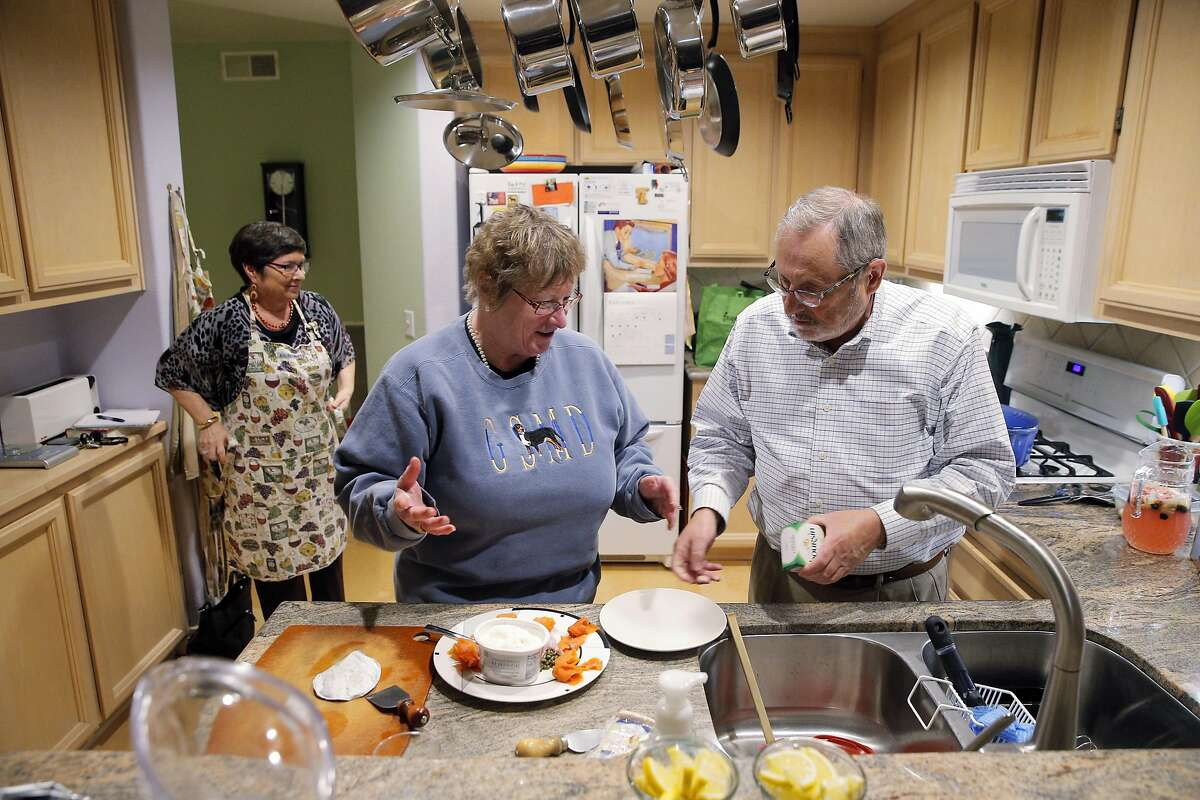 Lita Gloor-Little, center, chats with Doug Bachmann as Dawn Bachmann, left, continues to prepare dishes during a dinner gathering at the home of the Bachmanns in Martinez, Calif., on Sunday, February 19, 2017. A group of friends have been gathering for 15 years for bi-monthly Sunday dinners, usually for holidays and the Academy Awards. Then the election happened, and now the friends have named themselves the Gourmet Resistance Activist Networking Team. And the dinners will now serve as political grassroots action meetings.