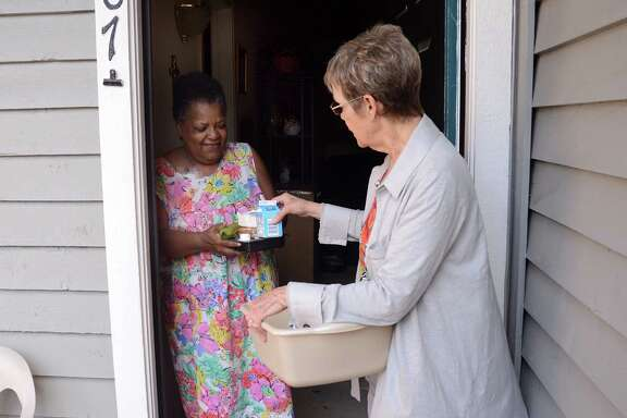 Sandy Andorka delivers a meal to Carol Thomas as part of the Northwest Assistance Ministries, 15555 Kuykendahl Road, Meals on Wheels program.