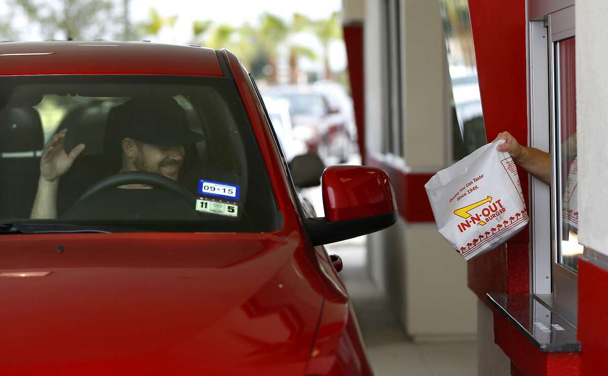 Josh Giehll celebrates in his truck as his drive-through order is handed to him during the grand opening Thursday Nov. 20, 2014 of San Antonio's first In-N-Out Burger. Giehll is originally from California, the birth place of the burger chain. The local store, located on Culebra just outside Loop 1604, opened at 9 a.m. because of the large crowds of people already in line for the store's normal 10 a.m. opening.