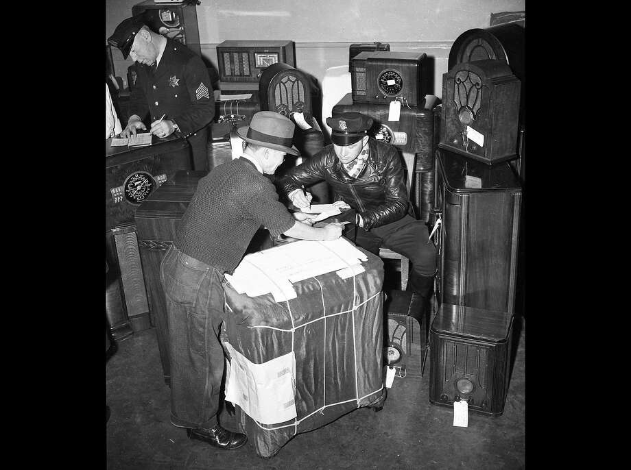 Dec. 29, 1941: A man identified as M. Shinagawa surrenders his short wave radio at the SFPD Northern Station, to police officer Frank Dickmeyer. Photo: Chronicle File Photo, The Chronicle