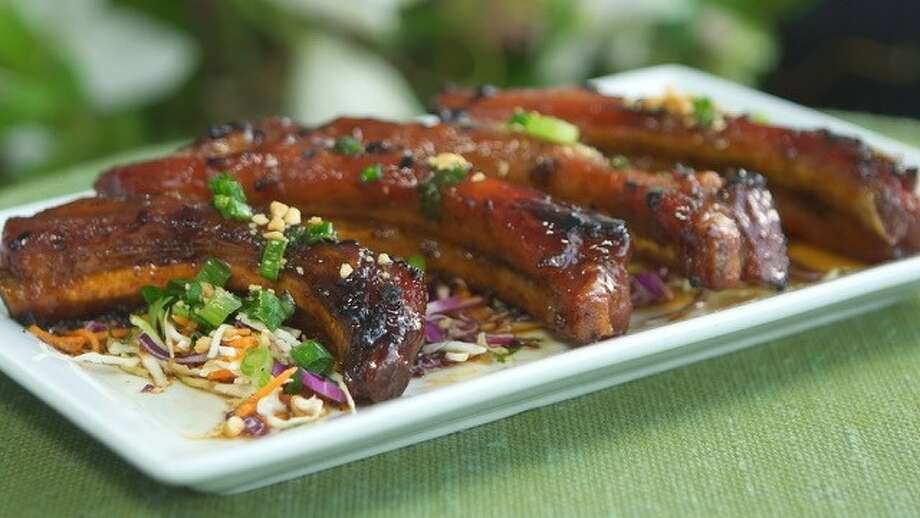 Charcoal grilled Suon Nuong (Baby Back Ribs) prepared with a luscious lemongrass-garlic rub and finished in a honey glaze with peanuts and scallions at Le Colonial in the River Oaks area.