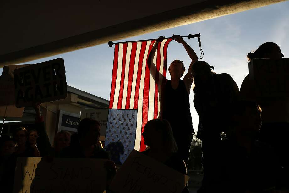 A demonstrator holds an American flag during a rally at San Francisco International Airport against President Trump's travel ban on Jan. 28. Photo: Stephen Lam, Getty Images