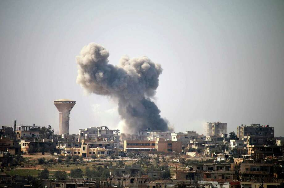 Smoke billows in the distance following reported air strikes on the southern Syrian city of Daraa on February 23, 2017. / AFP PHOTO / MOHAMAD ABAZEEDMOHAMAD ABAZEED/AFP/Getty Images Photo: MOHAMAD ABAZEED, Stringer / AFP/Getty Images / AFP or licensors