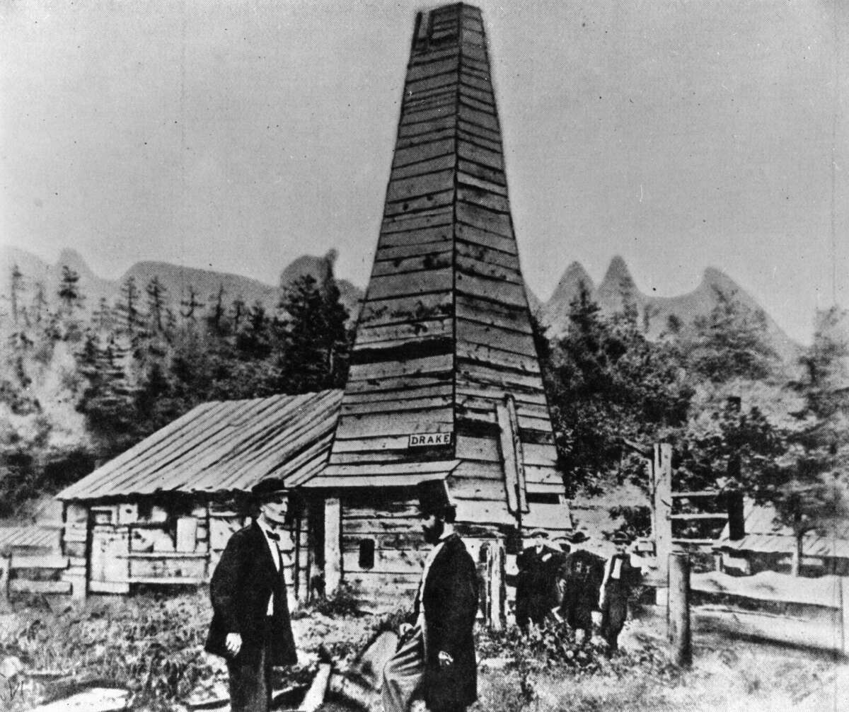 Jan. 1, 1860: Colonel Edwin Laurentine Drake (1819 - 1880), in top hat, talking to an engineer in front of his oil well at Titusville, Pennsylvania. In the background are 'Uncle Billy' Smith and his two sons who drilled the well, striking oil at 69 feet on August 27th, 1859. The US petroleum industry started here.