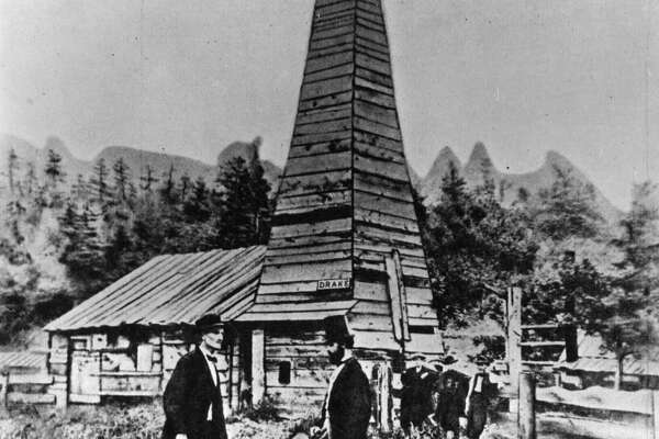 circa 1860:  Colonel Edwin Laurentine Drake (1819 - 1880), in top hat, talking to an engineer in front of his oil well at Titusville, Pennsylvania.  In the background are 'Uncle Billy' Smith and his two sons who drilled the well, striking oil at 69 feet on August 27th, 1859. The US petroleum industry started here.  (Photo by Hulton Archive/Getty Images)