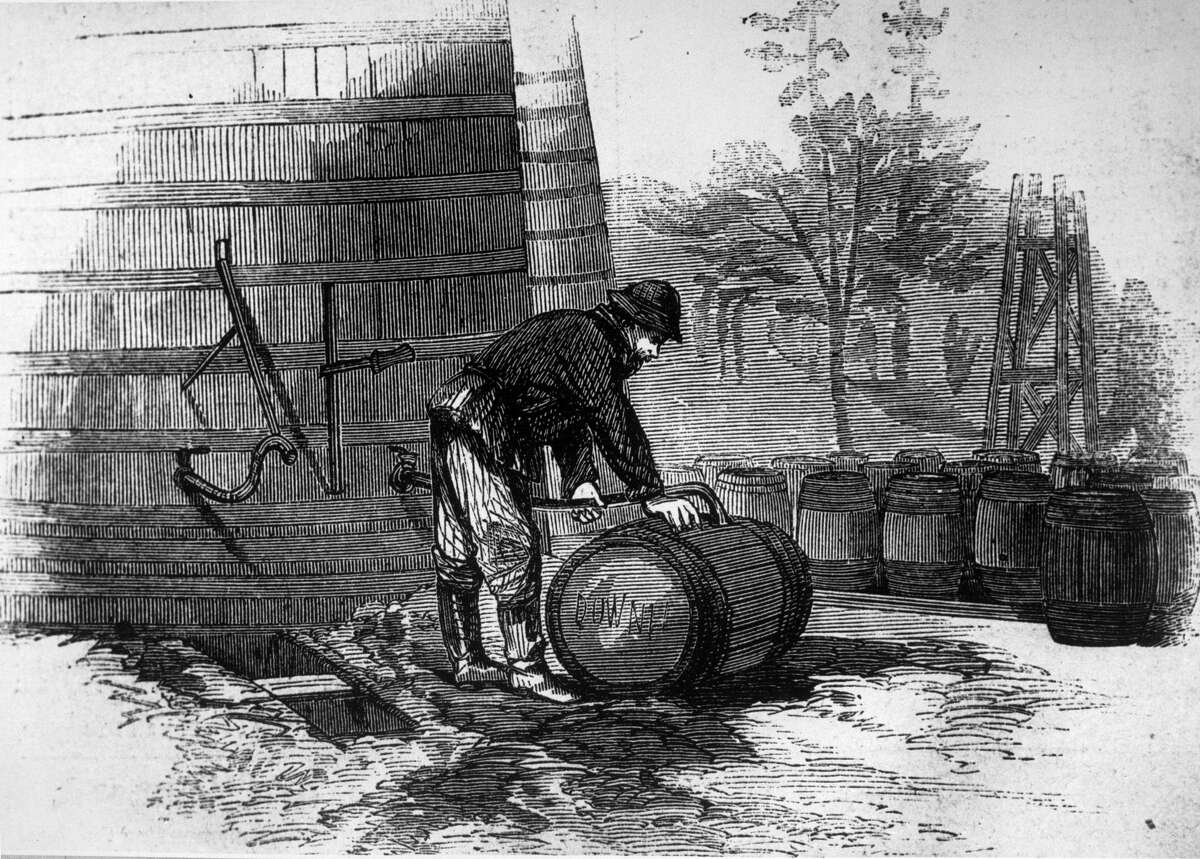 Jan. 1, 1870: A man filling barrels with oil from a large wooden tank on site at an oil-field.