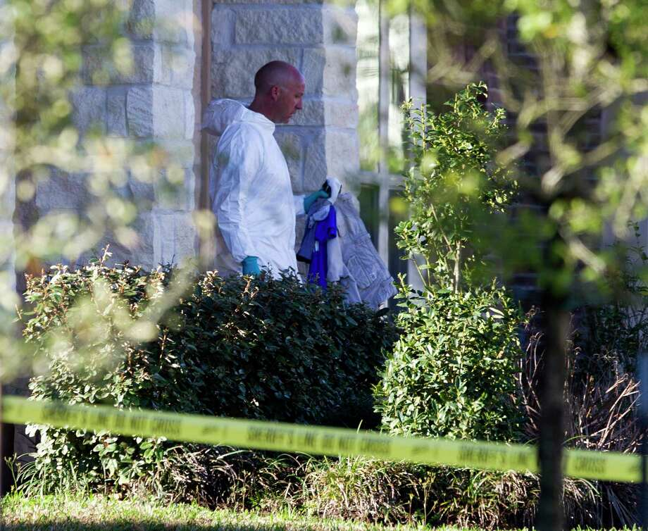 An investigator with the Montgomery County Sheriff's Office carries items away the scene of an officer involved shooting on Chestnut Meadow Court Wednesday, Feb. 22, 2017, in Conroe. An MCSO officer shot and killed a man that stabbed his wife to death. Law enforcement was alerted to the incident after the family's 11-year-old son called 911. Photo: Jason Fochtman, Staff Photographer / © 2017 Houston Chronicle