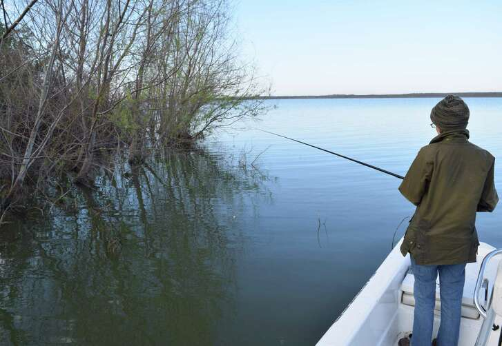 Fishing close to a shrub-covered shoreline at Choke Canyon Reservoir, Dr. Catherine Cook of San Antonio tests her angling skills against shallow water crappie that will be engaging in their annual spring spawn during the next couple of months.