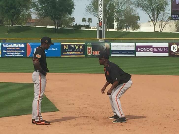 Vince Coleman, who stole 752 bases in his big-league career, crouches as he instructs Giants outfield hopeful Wynton Bernard.