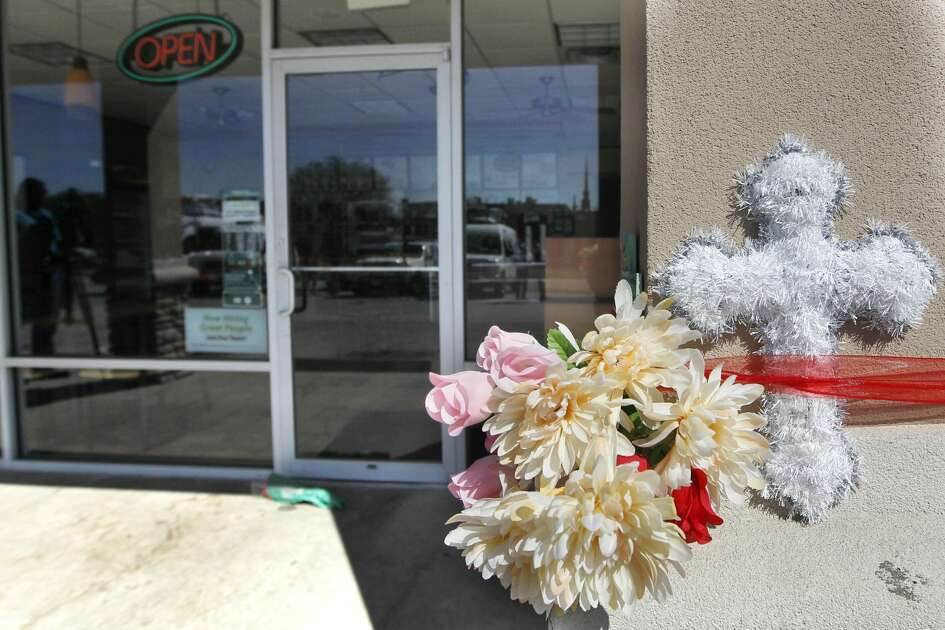 Flowers are placed after a Subway clerk was killed by two men during a robbery in the 3900 block of Broadway Street around 8 p.m. Wednesday in Houston.  ( J. Patric Schneider / For the Chronicle )