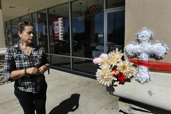 Diana Balderas places a candle outside a Subway in the 3900 block of Broadway on Thursday, Feb. 23, 2017, in Houston.   A clerk was killed at that location by two men during a robbery around 8 p.m. Wednesday.   ( J. Patric Schneider / For the Chronicle )