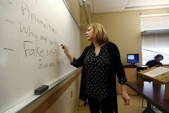 In this Friday, Jan. 20, 2017, photo, Pat Winters Lauro, a journalism professor at Kean University in Union, N.J., leads a class discussion talking about fake news. Teachers from elementary school through college have been ramping up media literacy training to recognize bogus reports and understand their potential to weaken civic culture. (AP Photo/Julio Cortez)