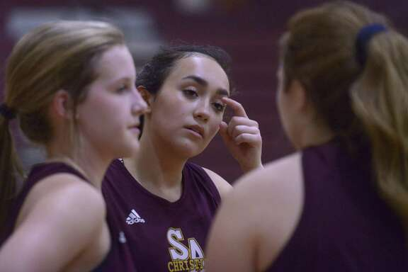 Sarah Gwin (middle) speaks with teammates during a San Antonio Christian practice. Gwin leads the Lions with 17.7 ppg.