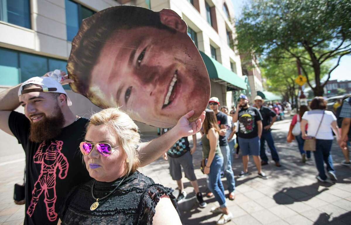 Erick Bock, left, holds a cutout of boxer Canelo Alvarez as he and his mother, Sylvia Bock, line up out outside Minute Maid Park to attend a press conference promoting the fight between Canelo Avlarez and Julio Cesar Chavez, Jr., on Thursday, Feb. 23, 2017, in Houston.