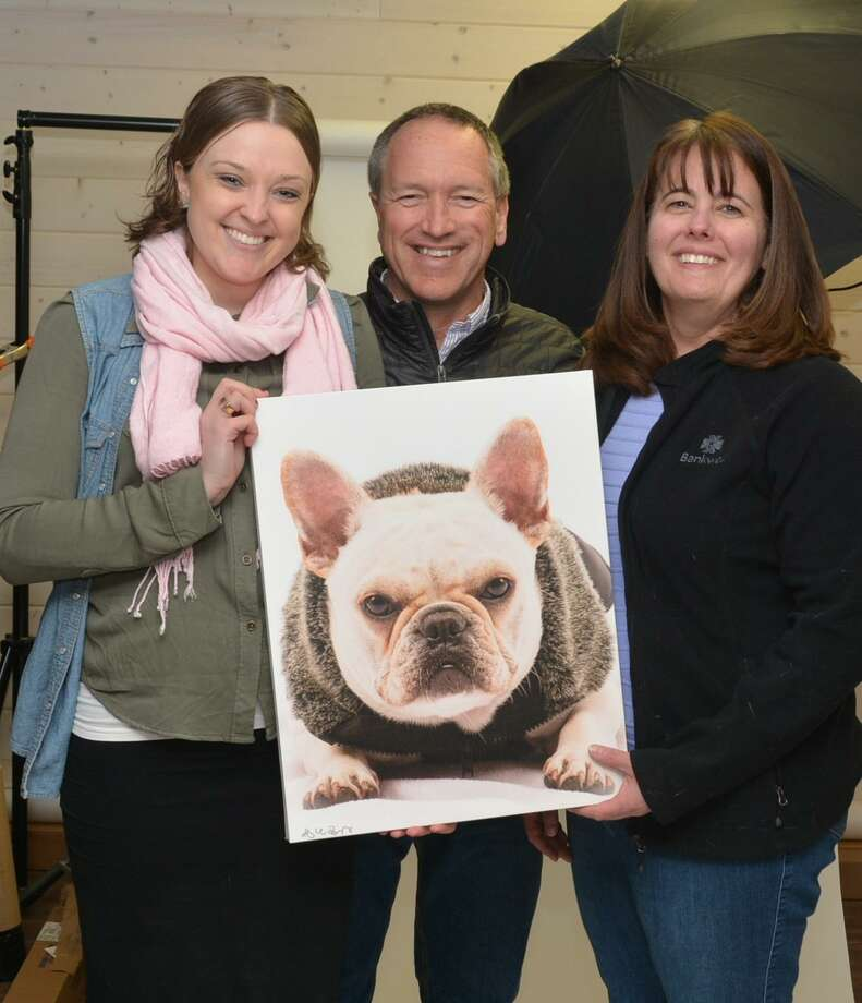 Bankwell Marketing Assistant Lucy French, photographer Mike Bagley and Ann Mitrione, Bankwell in Wilton branch manager, pose with a photo of a dog seeking adoption. Photo: Contributed Photo