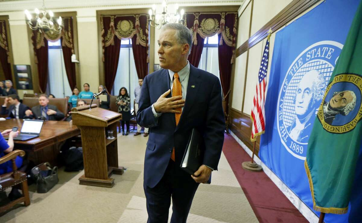 Washington Gov. Jay Inslee walks away from the podium after talking to reporters, Thursday, Feb. 23, 2017, at the Capitol in Olympia, Wash., after he signed an executive order to ensure that state workers don't help carry out President Donald Trump's immigration policies. Trump has said he wants to expand the number of deportations of people in the country illegally, and Inslee said Thursday that his order reaffirms the state's commitment to tolerance and ensures that state workers roles are to provide services for residents and not to enforce immigration statutes. (AP Photo/Ted S. Warren)