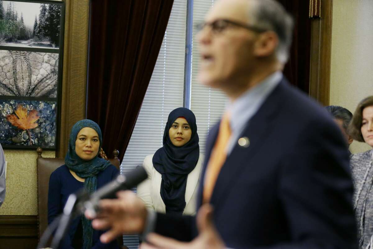 Rokaih Vansot, left, a member of the Washington state chapter of the Council on American-Islamic Relations, stands with Aishah Bomani, center, the principal of Seattle's Makkah Islamic School, as they listen to Washington Gov. Jay Inslee, right, talk to reporters, Thursday, Feb. 23, 2017, at the Capitol in Olympia, Wash. Inslee signed an executive order to ensure that state workers don't help carry out President Donald Trump's immigration policies. (AP Photo/Ted S. Warren)