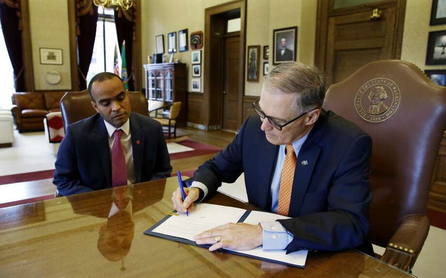 Washington Gov. Jay Inslee right, signs an executive order, Thursday, Feb. 23, 2017, in his office at the Capitol in Olympia, Wash., as general counsel Nick Brown looks on at left. The order ensures that state workers don't help carry out President Donald Trump's immigration policies. Trump has said he wants to expand the number of deportations of people in the country illegally, and Inslee said Thursday that his order reaffirms the state's commitment to tolerance and ensures that state workers roles are to provide services for residents and not to enforce immigration statutes. (AP Photo/Ted S. Warren) Photo: Ted S. Warren/AP