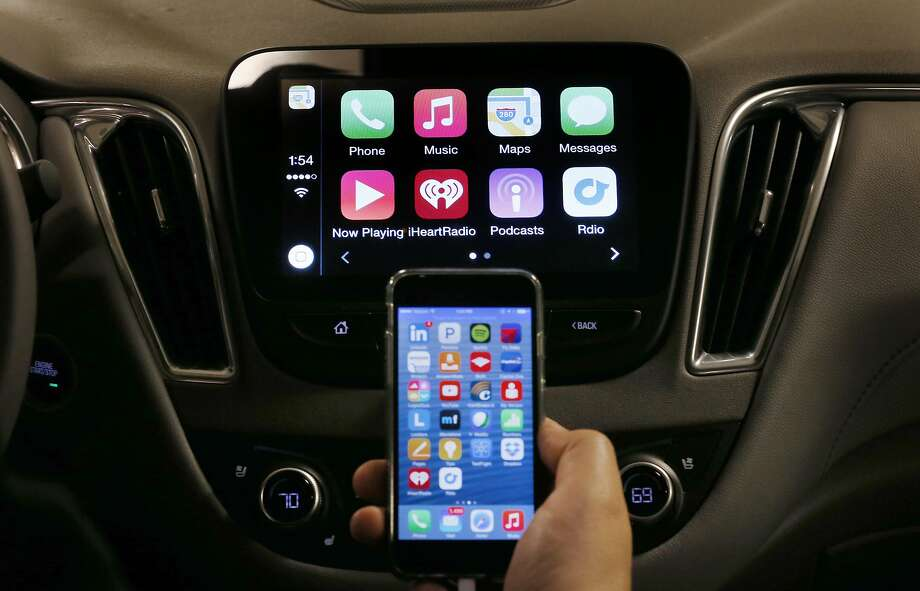 FILE - In this May 26, 2015 file photo, an iPhone is connected to a 2016 Chevrolet Malibu equipped with Apple CarPlay apps, displayed on the car's MyLink screen, top, during a demonstration in Detroit.  The rapidly evolving in-car infotainment and navigation systems can be bewildering for all but the most tech-savvy car buyers. The average vehicle on U.S. roads is 11 years old; that means many people last went car shopping before iPhones were invented. (AP Photo/Paul Sancya) Photo: Paul Sancya, Associated Press