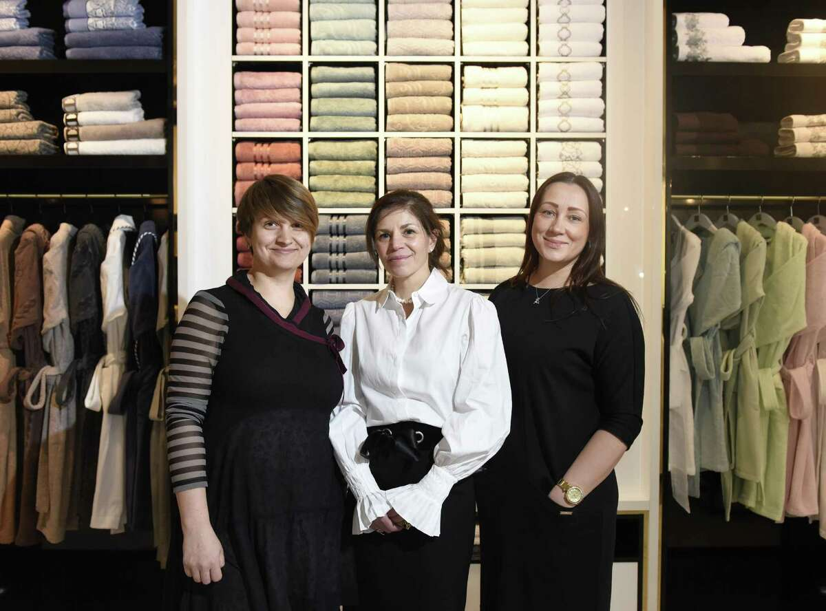 Designer Victoria Ivanova, left, Boutique Manager Paula Davitch, center, and Manager of International Business Development Julia Jarray pose in front of a colorful array of Egyptian cotton bath towels at Togas House of Textiles in Greenwich, Conn. Monday, Feb. 14, 2017. The Greece-based retailer is opening its first U.S. location in Greenwich, selling luxury home textiles ranging from sheets and curtains to bathrobes and towels.
